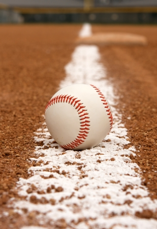 Baseball on the chalk line with third base beyond Фото со стока