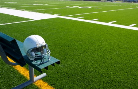 american football field: American Football Helmet on the Bench with the field beyond