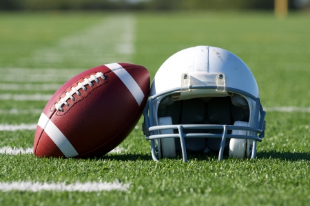 american football field: American Football and Helmet on the Field
