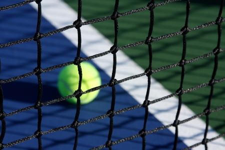 Tennis Court Net close up with the ball and court in background Stock Photo
