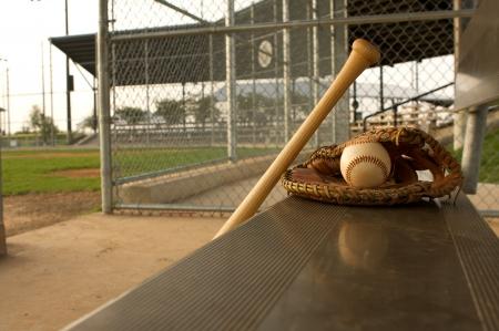 guante de beisbol: Bate de b�isbol y guantes en el banco de la caseta