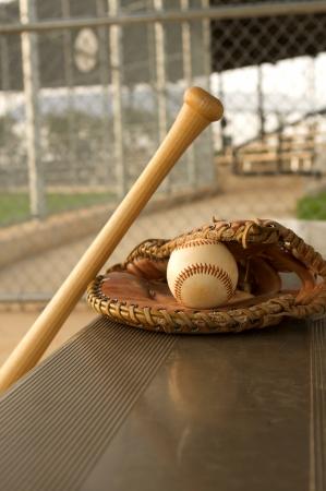 guante de beisbol: Bate de béisbol y guantes en el banco de la caseta