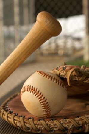 baseball dugout: B�isbol en un guante y un bate de b�isbol en el dugout Foto de archivo