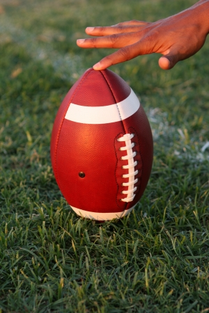 kickoff: American Football propped up and held for kickoff