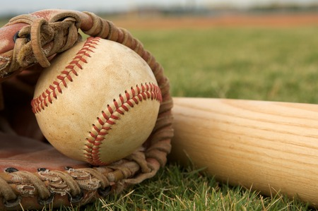 Baseball in a Glove near the Baseball Bat photo