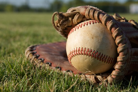 outfield: Baseball in a Glove on the outfield grass