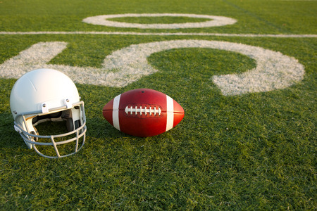 American Football and Helmet on the Field with the Fifty Yard Line