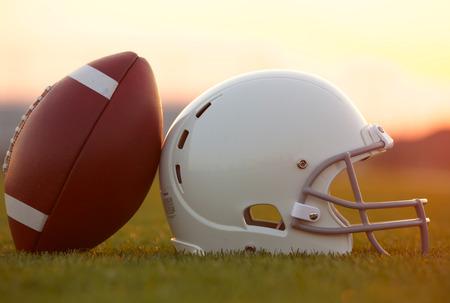 American Football en helm op het veld bij zonsondergang Stockfoto