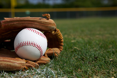 New Baseball in a Glove in the Outfield Stock Photo - 26507982