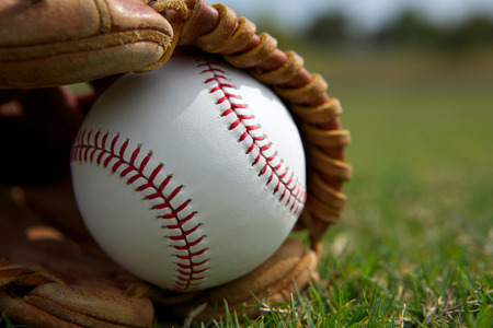 New Baseball in a Glove in the Outfield Stock Photo - 26507985