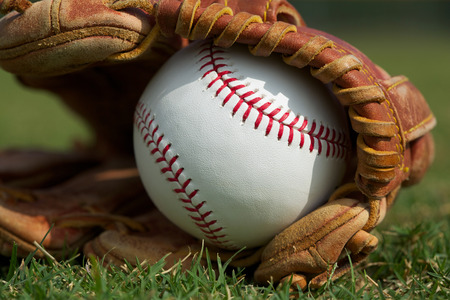 New Baseball in a Glove in the Outfield Stock Photo - 26507990