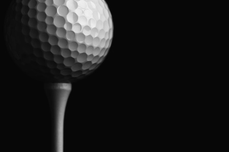 pelota de golf: Pelota de golf Teed Up Close Up contra una pared Negro Foto de archivo