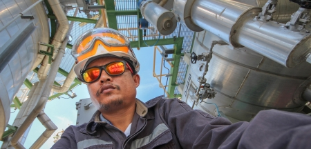 A man with personal protection suit in refinery plant Stock Photo