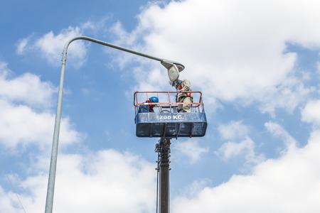 Electrical technician to repair street lightin by boom lift 스톡 콘텐츠