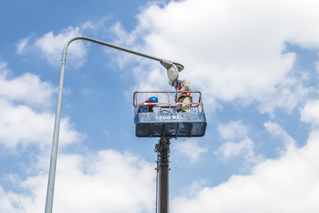 Electrical technician to repair street lightin by boom lift Stock Photo