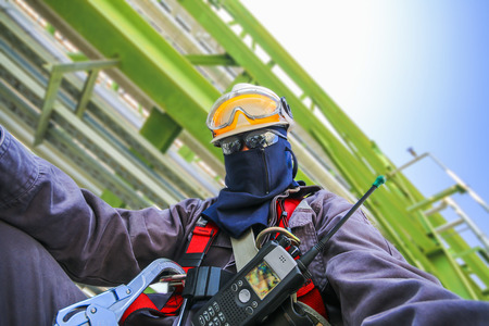 Man with safety personal protection equipment on structure in industrial plant background Stock Photo