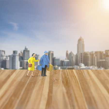 Miniature people figure ,Husband and wife tourist walking on honey moon time , wooden floor and city background