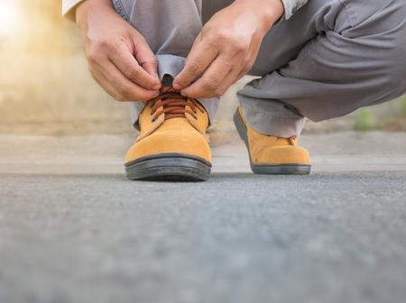 calzado de seguridad: Close up of The man wears safety shoes on street with green light sun flare Foto de archivo