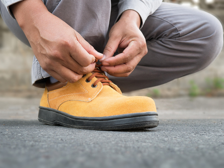 calzado de seguridad: Close up of The man siting to wears safety shoes on street