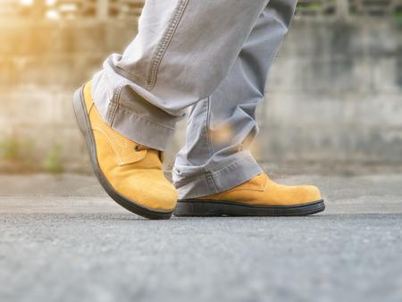 calzado de seguridad: Close up of man wears safety shoes standing on street with green light sun flare Foto de archivo