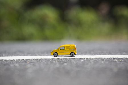 Miniatuur transport vrachtwagen, gele vrachtwagen op straat Stockfoto