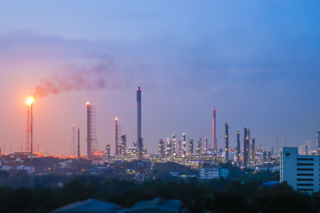 Twilight scene of Oil refinery plant , Light from Fire gas burning from flare structure , Land escape view of oil refinery plat on night time