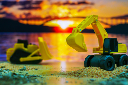 Construction engineering concept , Excavator machine toy and Truck toy working on construction field with silhouette sunset background