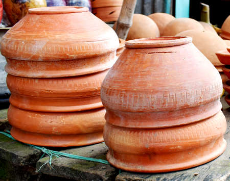 Traditional Handmade clay brown cups, pots and plates in Asian local market,Oriental bazaar. Old pottery. Exhibits ancient times.