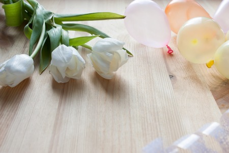 three white tulips and small air balloons on a light wooden background Stock Photo