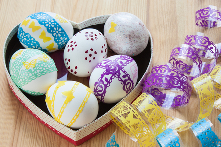 Easter eggs decorated in a box in the form of hearts, near ribbons stickers for decorating eggs, on a wooden background