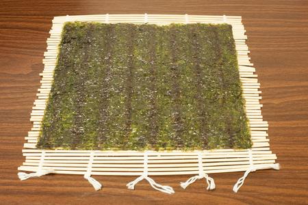 On a bamboo Mat, Nori sheets for sushi. Photo format horizontal Stock Photo