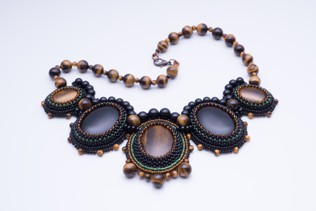 Necklace of handmade beads and natural stones Tiger eye of brown and agate black on a white background, copy-paste