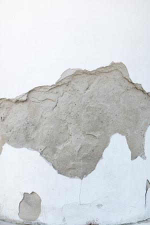 white wall background with peeling plaster, dark stain Banco de Imagens