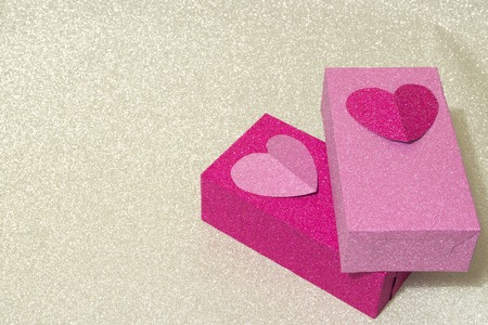 two brilliant boxes crimson and pink decorated with hearts on silver background Imagens
