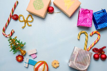 gift boxes, bags and alternative beaded Christmas tree with candy on blue background. Concept.