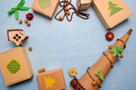 eco-friendly gifts and alternative Christmas tree made of twine on a blue background. The concept of cherish nature.