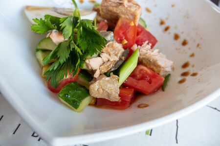 tuna, tomato and cucumber salad dressed with soy sauce. Shallow depth of field.