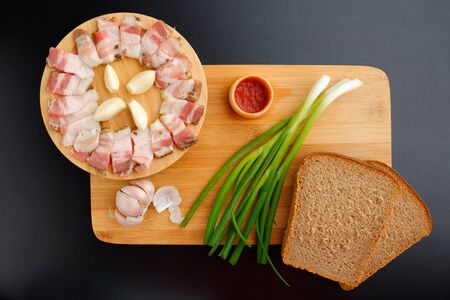 BACON WITH BREAD ONIONS AND KETCHUP ON A WOODEN BOARD ON A BLACK TABLE. Flatley.