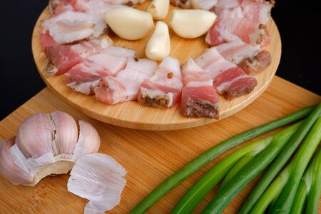 bacon with garlic and green onions on a wooden stand.