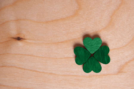 A four-leaf clover made of green hearts is laid out on a wooden background. Reklamní fotografie