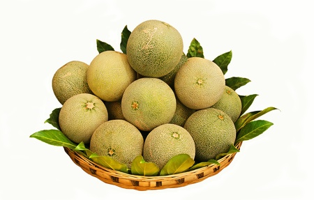 A wicker basket with round melons.