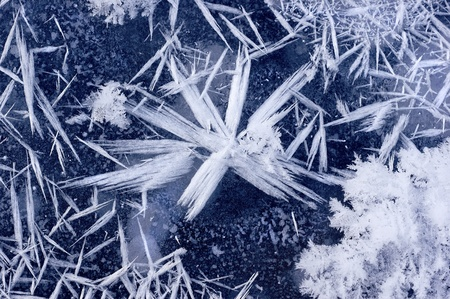 White acute snowflake on the blue ice.