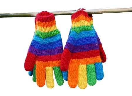 Knitted gloves in a rainbow striped hang on a stick. Stock Photo