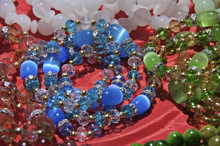 nephritis: Necklaces and bracelets made of semi-precious stones on a red background.