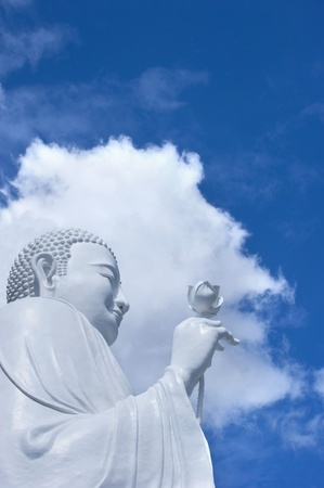 A huge white buddha statue in the sky and the clouds  Stock Photo