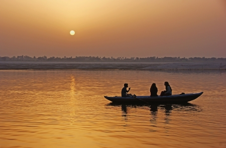 The boat with the people on the river at sunset. Stock Photo