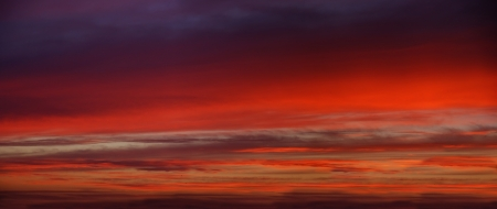 The sky at sunset is bright red-violet color.