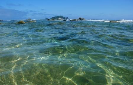 Transparent sea water stretches beyond the horizon. Stock Photo