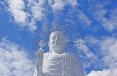 Sculpture of white Buddha with the lotus in a hand against the sky.