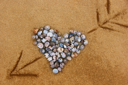 Heart is made of shells on the sand, and an arrow pierces right through